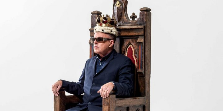 Suggs wearing suit crown on head sitting throne