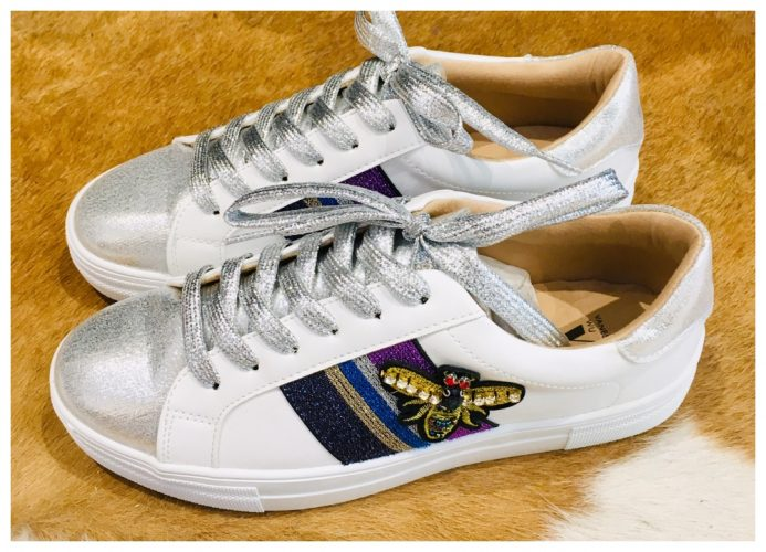 white trainers with bee emblem